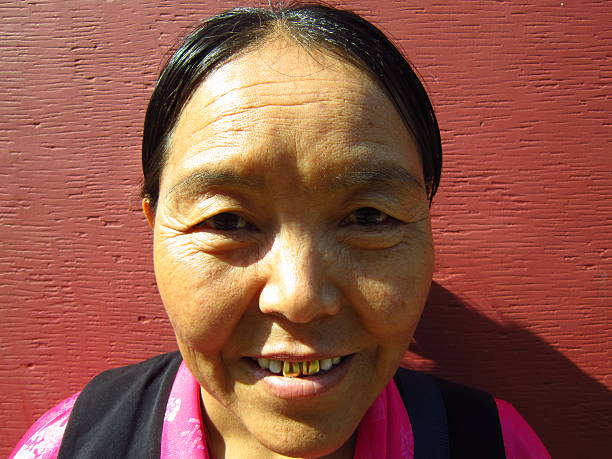 portrait of a middle aged tibetan woman with golden teeth. - gold tooth stock photos and pictures