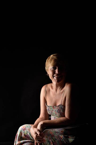 porträt eines mittleren alter frau - jumpsuit schwarz kurz stock-fotos und bilder