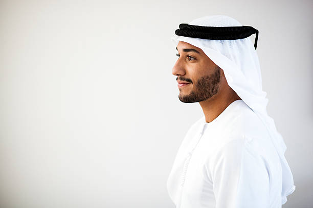 Portrait of a Middle Eastern man smiling to the left Close up portrait of Emirati wearing traditional clothing - kandura, kaffiyeh and agal. middle eastern culture stock pictures, royalty-free photos & images