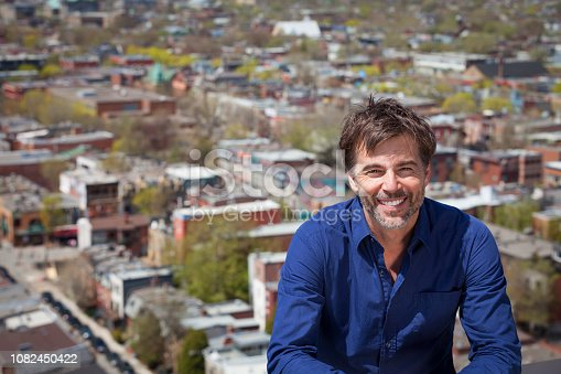 637538262istockphoto A portrait of a middle-aged man with a short beard smiling on a city background 1082450422