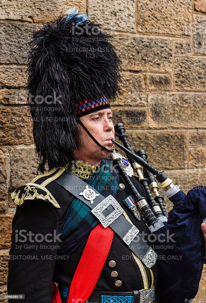 Portrait of a military dressed bagpiper playing the bagpipe stock photo