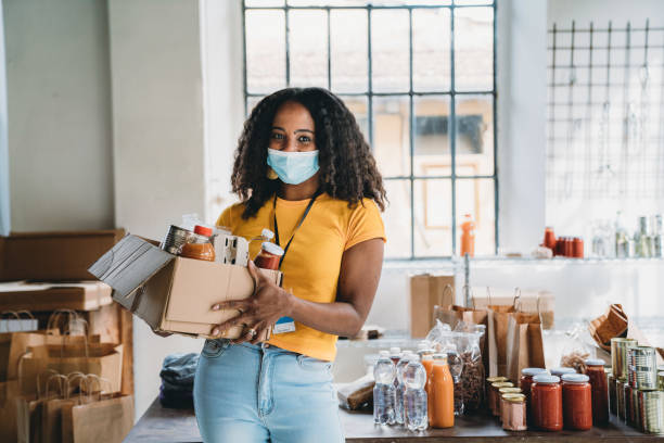 Portrait of a mixed race volunteer woman holding a cardboard box of food and drink at the food bank stock photo