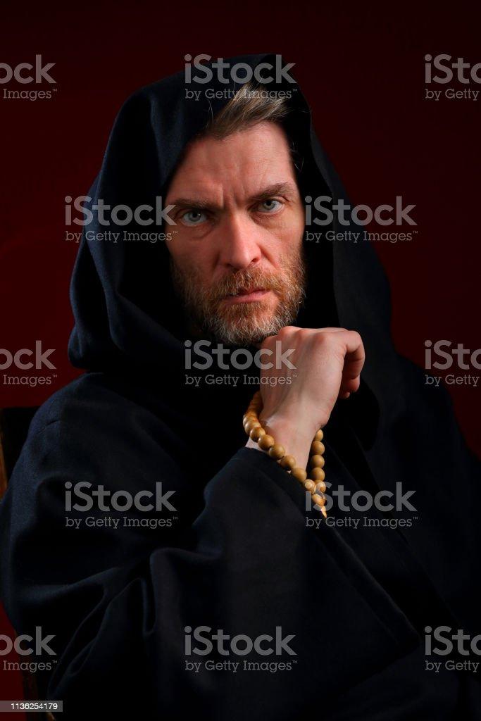 Retrato de uma monge em uma casmeia preta, com um rosário - foto de acervo