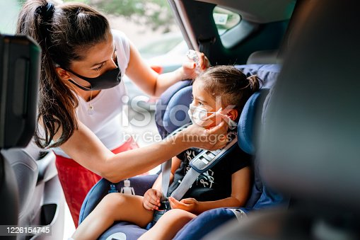 Portrait of a mother fastening her daughter safely in a car seat