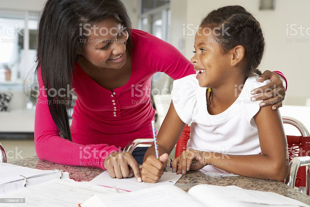 A portrait of a mother helping her daughter with homework royalty-free stock photo