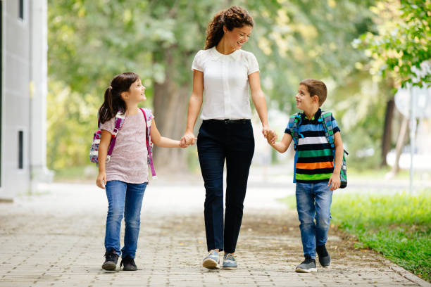Portrait of a mother taking her children to school stock photo