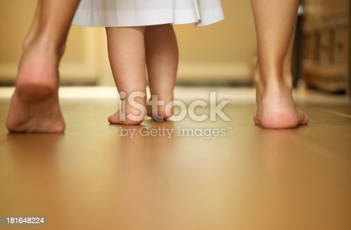 istock Portrait of a mother teaching baby to walk indoors 181648224