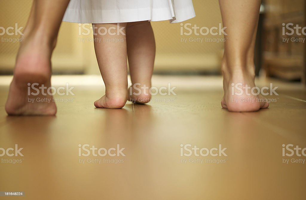 Portrait of a mother teaching baby to walk indoors stock photo