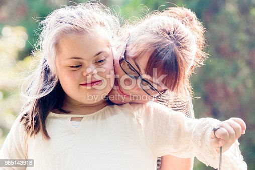 istock Portrait of a mother with her daughter of 12 years old with Autism and Down Syndrome in daily lives 985143918
