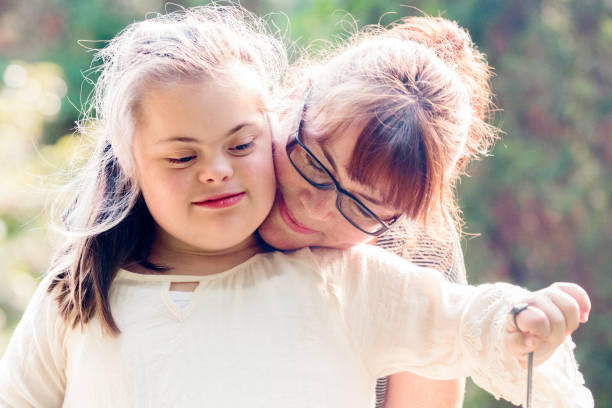 portrait of a mother with her daughter of 12 years old with autism and down syndrome in daily lives - manonallard stock photos and pictures