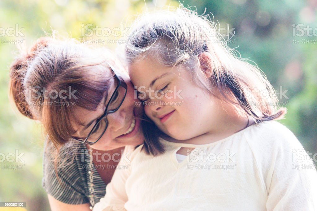 Portrait of a mother with her daughter of 12 years old with Autism and Down Syndrome in daily lives stock photo