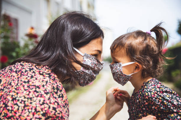 Portrait of a mother with her little daughter wearing surgical mask stock photo