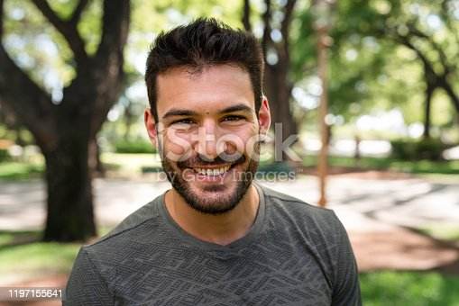 istock Portrait of a muscular young man in a public park 1197155641