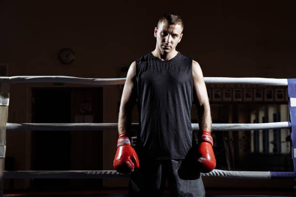 Portrait of a muscular young man in Boxing gloves in the ring stock photo