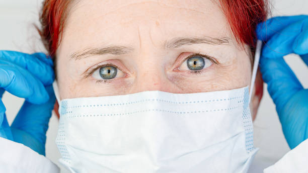 Portrait of a nurse adjusting her protective surgical mask stock photo
