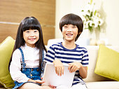 two cute asian children little boy and little girl sitting on couch holding digital tablet looking at camera smiling