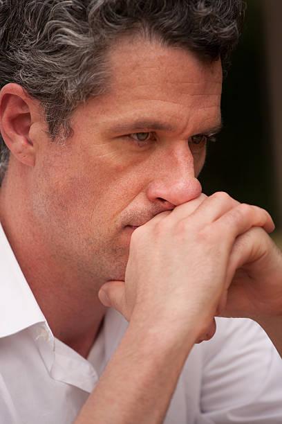 portrait of a pensive professional man deep in thought - foto's van hands stockfoto's en -beelden