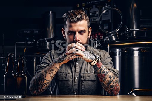Portrait of a pensive tattooed hipster male with stylish beard and hair in shirt in indie brewery.
