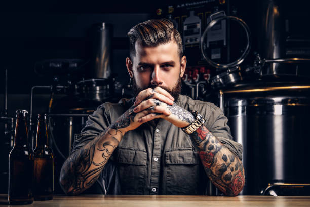 Portrait of a pensive tattooed hipster male with stylish beard and hair in the shirt in indie brewery. Portrait of a pensive tattooed hipster male with stylish beard and hair in shirt in indie brewery. bartender stock pictures, royalty-free photos & images