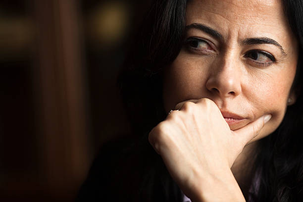portrait of a pensive woman with a furrowed brow - cynic stock pictures, royalty-free photos & images