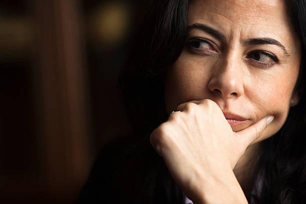 portrait of a pensive woman with a furrowed brow - achterdocht stockfoto's en -beelden