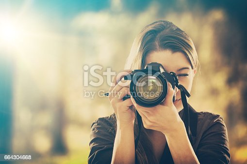 istock Portrait of a photographer covering her face with camera. 664304668