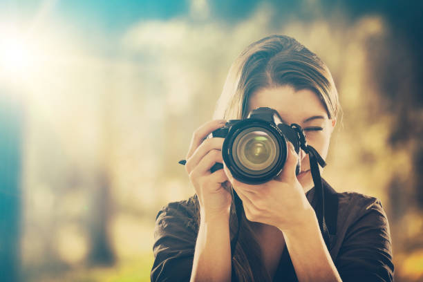 portrait of a photographer covering her face with camera. - camera photographic equipment stock photos and pictures