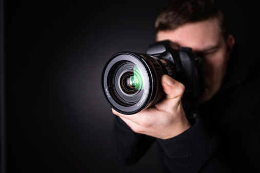 A photographer with a camera. Focus is on the lens.