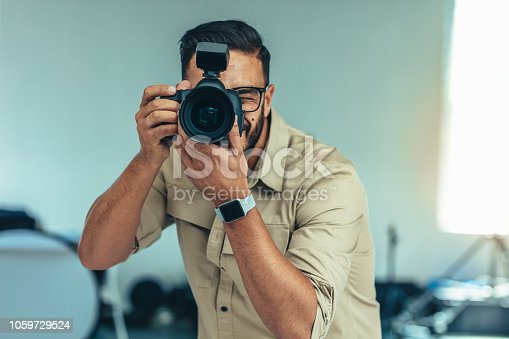 Photographer standing in position to take a photograph. Man looking into a digital camera for taking  a photograph.