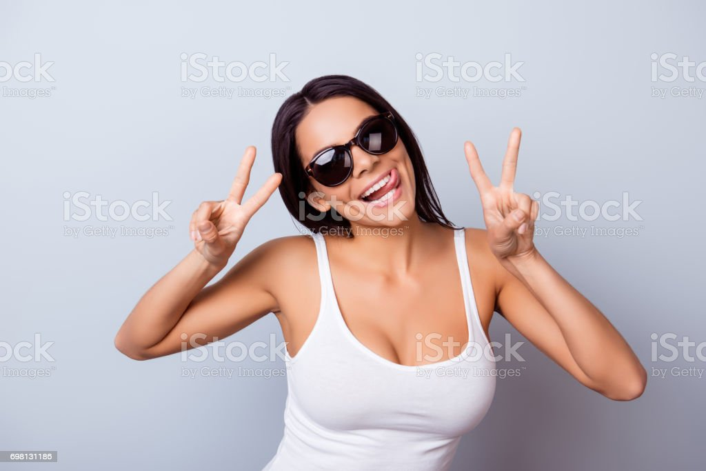Portrait of a playful young latin girl with tongue out. She is in a casual clothes and sunglasses, standing on the blue background stock photo