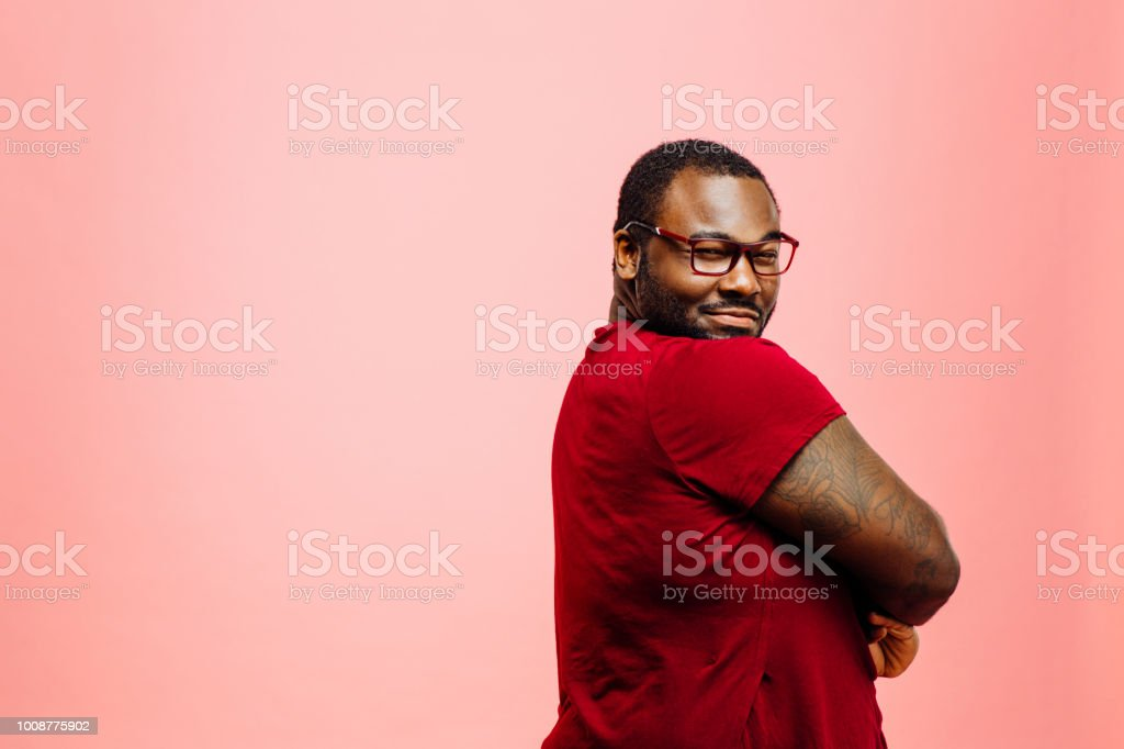 Portrait of a plus size man in red shirt and glasses looking back at camera stock photo