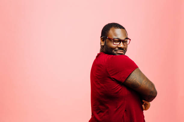 portrait of a plus size man in red shirt and glasses looking back at camera - bold stock photos and pictures