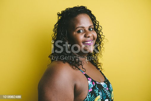 Portrait of a plus size woman on yellow background