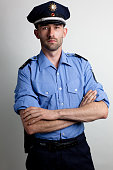 portrait of a policeman in blue uniform arms crossed