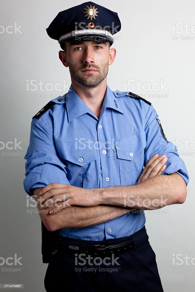 portrait of a policeman in blue uniform arms crossed stock photo