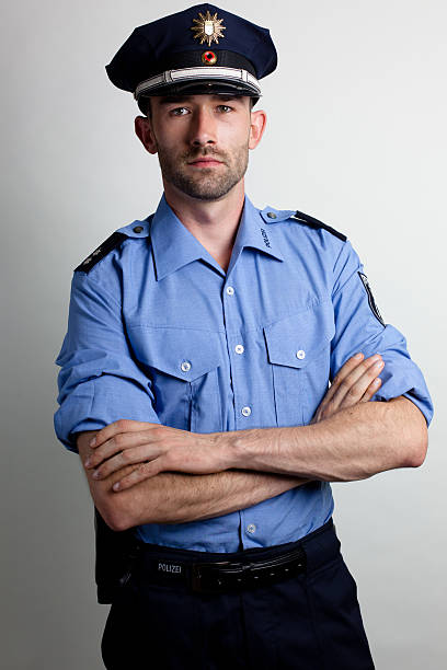 portrait of a policeman in blue uniform arms crossed portrait of a policeman in uniform police uniform stock pictures, royalty-free photos & images