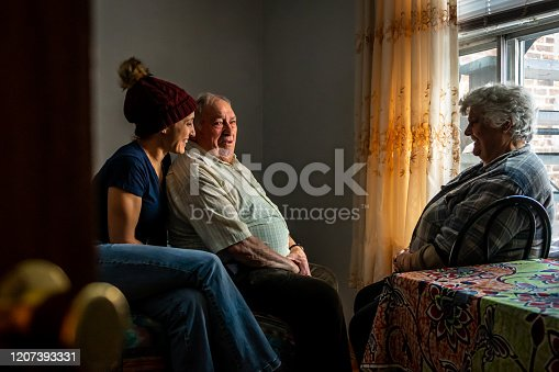 Portrait of an elderly couple talking with their daughter by a window in their room.
