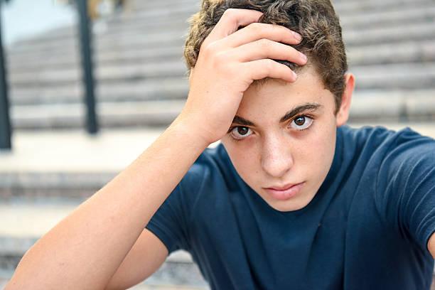 portrait of a posing pensive male teenager - schulkind nur jungen stock-fotos und bilder