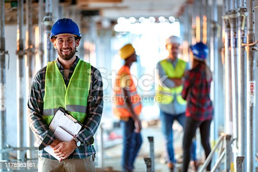 Portrait Of young Construction Worker On Building Site looking at the camera with smile. Professional engineer in safety equipment at construction site