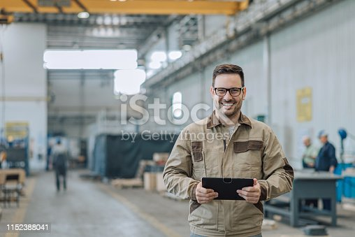 Portrait of a positive engineer at large factory hall.