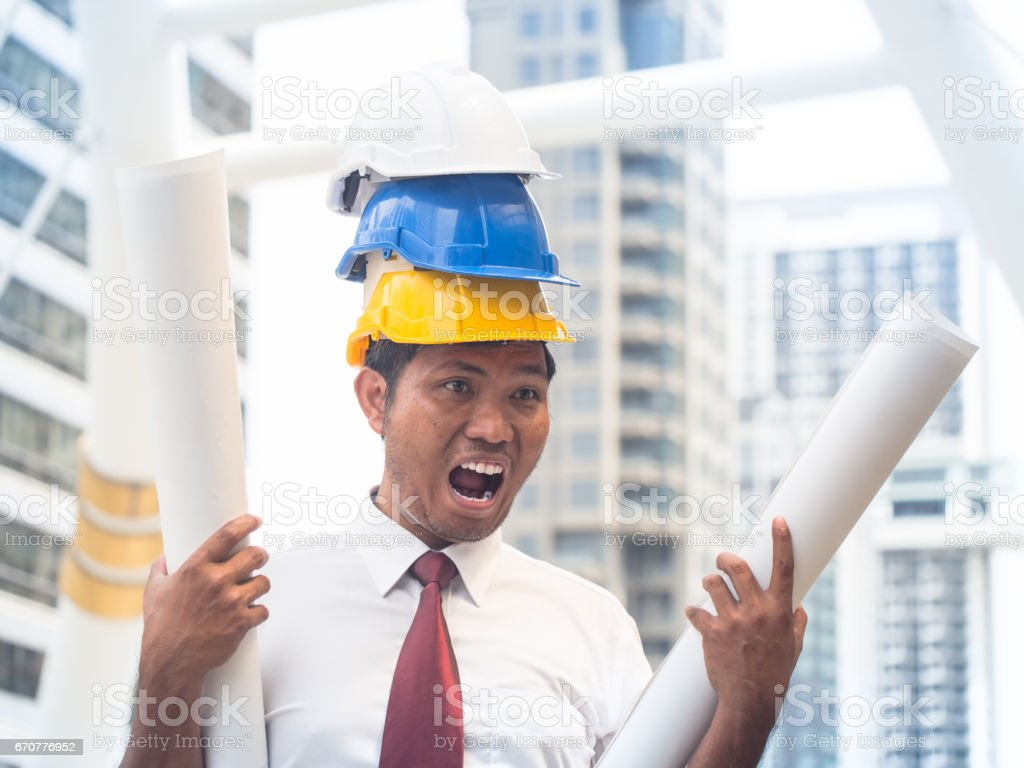 Portrait of a Powerful engineer with triple safety helmets and hold architect rolls. Engineer concept. stock photo