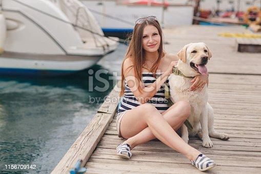 Beautiful young pregnant woman,a brunette with long straight hair and brown eyes,wears a gold neck chain and cross,sits on the dock near the sea on the backdrop of the yacht with his dog breed white Labrador