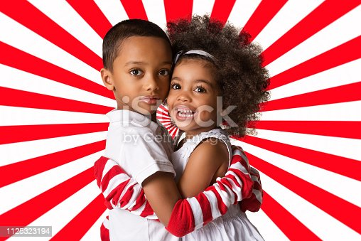 istock Portrait of a preschool african-american siblings hugging each other. Two kids on geometric background 1125323194