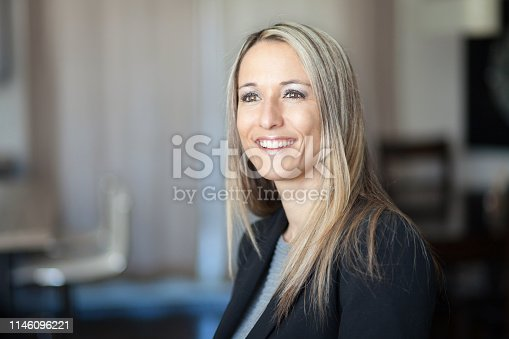 istock Portrait Of A Pretty Blond Woman Smiling and Looking away. She is lost in thoughts 1146096221