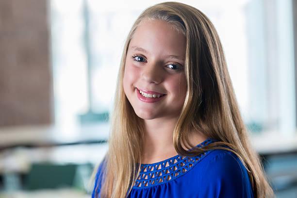 portrait of a pretty blonde preteen girl in a classroom - high school bilder stock-fotos und bilder