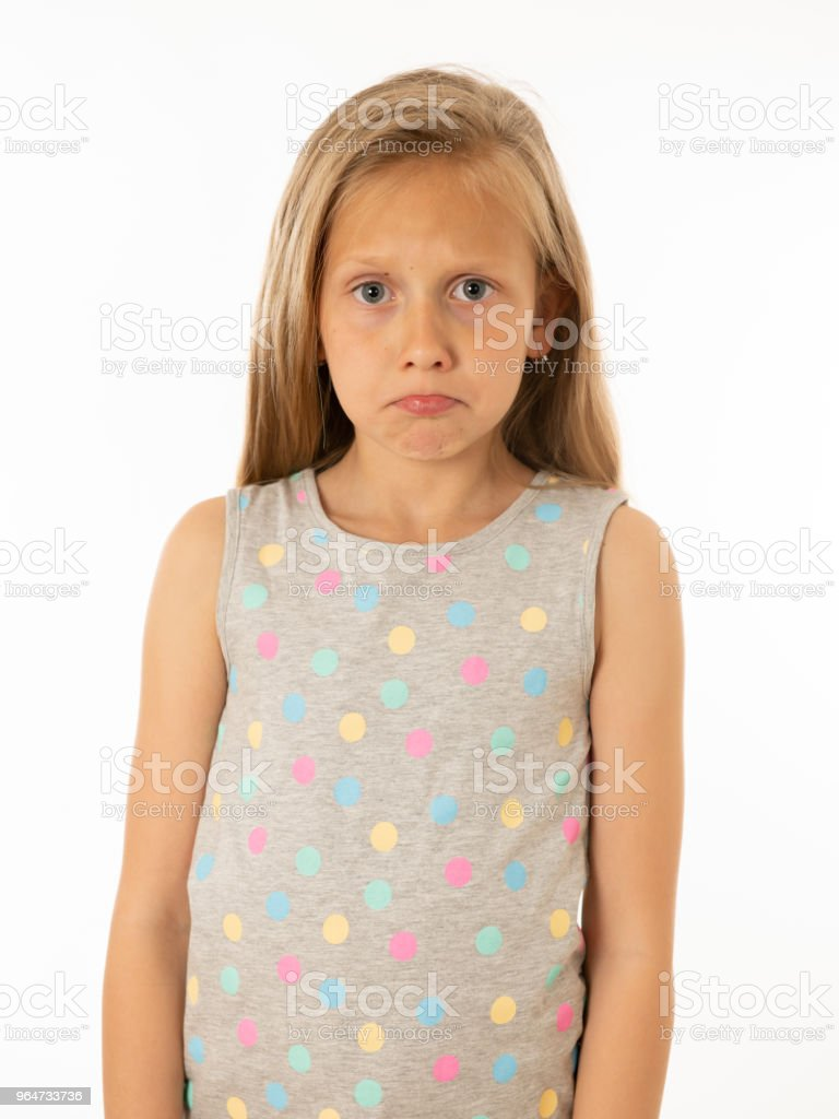 Portrait of a pretty bullied, depressed, alone, tired, stressed young child looking unhappy and sad. Isolated withe background. Human emotions, facial expressions, body language and bulling royalty-free stock photo