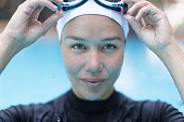 Athletic woman holding her goggles after finishing swim laps in the water.