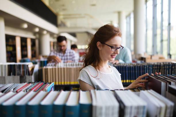 retrato de un libro de lectura de chica bastante sonriente en biblioteca - library fotografías e imágenes de stock