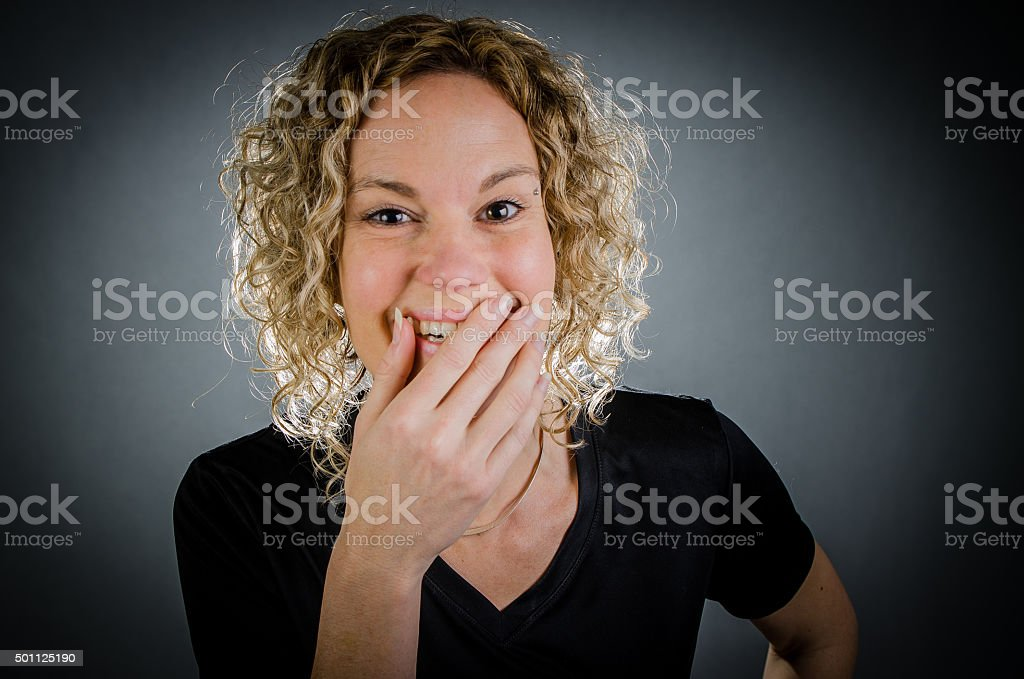 Portrait of a pretty woman laughing in studio gray background stock photo