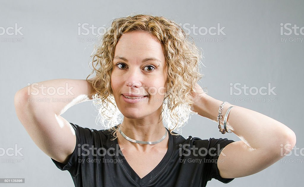 Portrait of a pretty woman playing with hair in studio stock photo